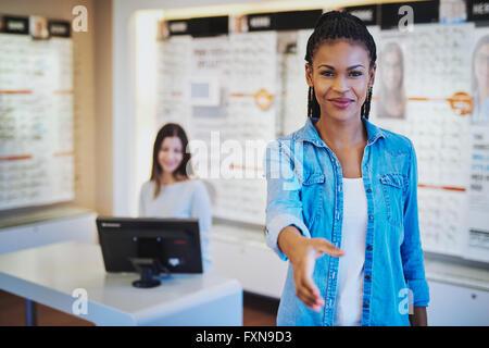 Jeune femme africaine vous accueillir dans son magasin d'optométrie, la main étendue et le sourire chaleureux Banque D'Images