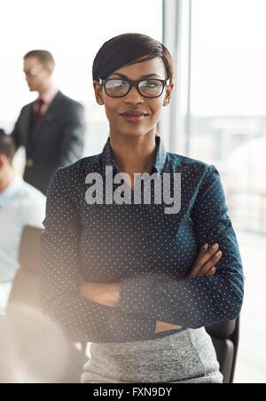 Smiling business woman avec exécutif confiant expression et bras croisés près de la table de conférence avec des Banque D'Images