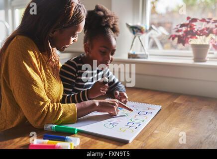 Femme et enfant alphabet d'apprentissage à la maison, mère et fille noire Banque D'Images