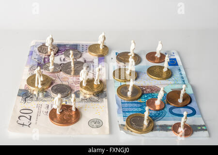 Les figures de gens debout sur l'euro et livres monnaies et billets Banque D'Images