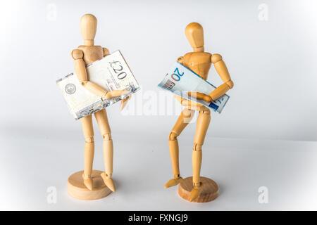 Mannequins en bois avec des livres et de l'euro dans les mains Banque D'Images
