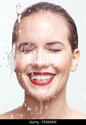 Femme souriante avec de l'eau dégoulinant sur son visage Banque D'Images