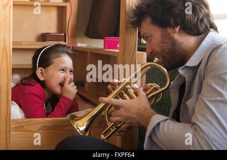 Père à jouer de la trompette pour little girl Lying in Bed Banque D'Images