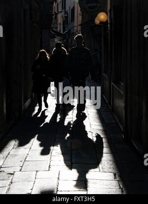 Piétons et leurs ombres dans une ruelle, éclairé, Venise, Vénétie, Italie Banque D'Images