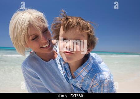 Portrait de garçon tirant un visage et sa mère sur la plage, Majorque, Espagne Banque D'Images