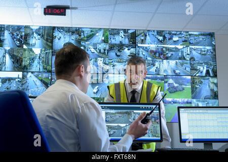 Les gardes de sécurité à la discussion en salle de contrôle de sécurité avec mur vidéo Banque D'Images