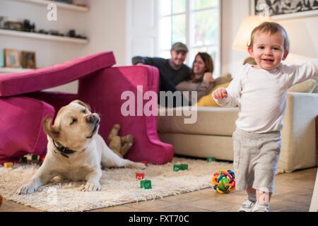 Bébé garçon et chien jouant à fort fait à partir de canapé coussins, smiling at camera