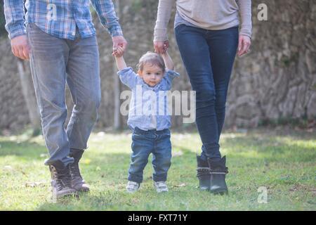 La section basse de parents holding baby boys mains Banque D'Images