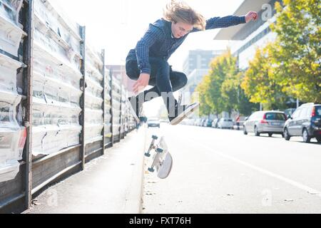 Young male skateboarder urbain faisant du skateboard jump sur route Banque D'Images