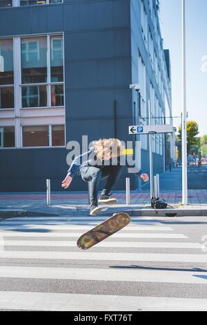 Young male skateboarder urbain faisant du skateboard jump sur passage pour piétons Banque D'Images
