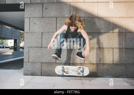 Young male skateboarder urbain faisant le skate jump trick skateboard ci-dessus Banque D'Images