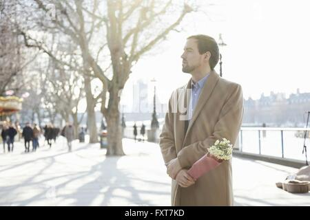 Mid adult man standing outdoors, holding bunch of flowers Banque D'Images