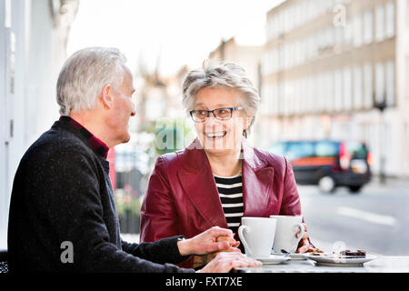Romantic senior couple holding hands at sidewalk cafe Banque D'Images