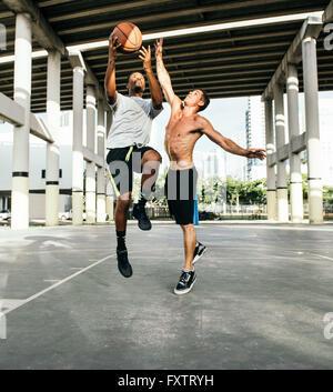 Les hommes sur un terrain de basket-ball Basket-ball pour le saut Banque D'Images