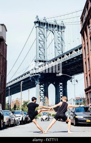 Deux hommes de vous pencher sur le côté en position de yoga en face du pont de Manhattan, New York, USA Banque D'Images
