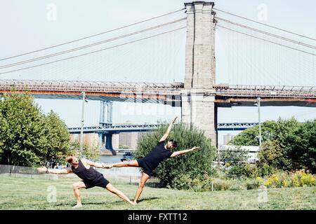 Deux hommes de vous pencher sur le côté en position de maintien de pied de yoga en face du pont de Brooklyn, New Banque D'Images