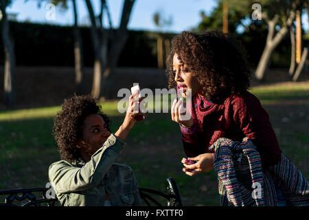 Les amis de park, woman applying Lip Gloss, à la recherche d'un ami dans le smartphone Blackberry Banque D'Images