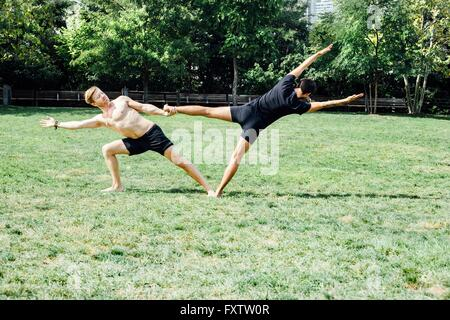 Deux hommes pratiquant le yoga pied position hold in park Banque D'Images