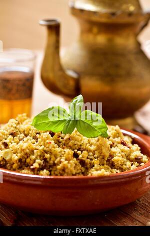 Libre d'un bol en terre cuite avec du couscous aux légumes, des verres décorés avec du thé et une théière d'or sur Banque D'Images