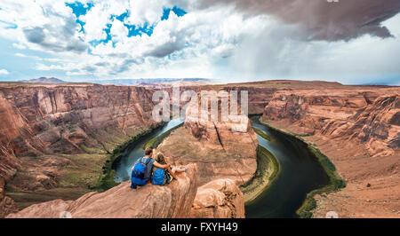 Jeune couple assis sur un rocher et à la recherche sur la centrale Horseshoe Bend, coude de la rivière Colorado, Banque D'Images
