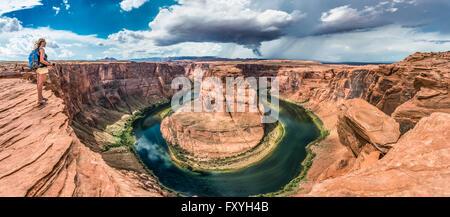 Tourist sur un rocher surplombant la centrale Horseshoe Bend, coude de la rivière Colorado, King Bend, Glen Canyon Banque D'Images
