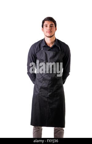 Jeune cuisinier ou serveur posant, le port de tablier noir et chemise isolé sur fond blanc