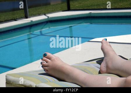 Pieds d'une femme mature de porter du vernis à ongles sur ses orteils pour correspondre à la piscine de couleur. Banque D'Images