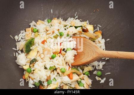 Gros plan du poulet, l'oeuf et de légumes riz sauté dans un wok avec une cuillère en bois Banque D'Images