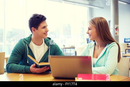 Les élèves heureux avec un ordinateur portable et des livres de bibliothèque Banque D'Images