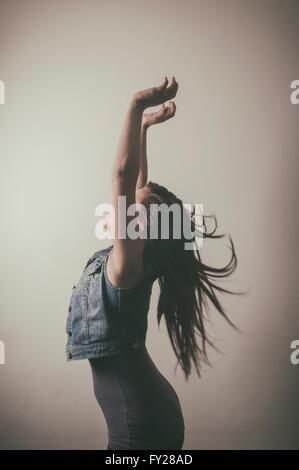 Jeune femme extatique raising arms Banque D'Images