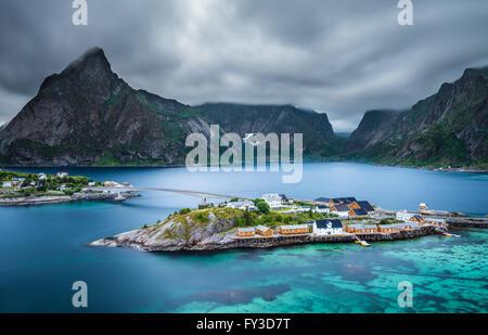 Olstind montage au-dessus des cabines jaunes et jaunes eaux de Sakrisoy village de pêcheurs sur les îles Lofoten en Norvège au soir bl