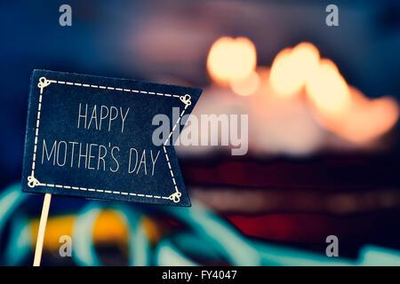 Libre d'une pancarte en forme de drapeau noir avec le texte heureux le jour de mères et un gâteau recouvert de bougies Banque D'Images