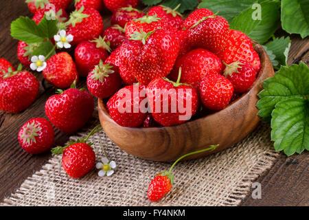 Tasse avec des fraises fraîches sur la table en bois. Banque D'Images