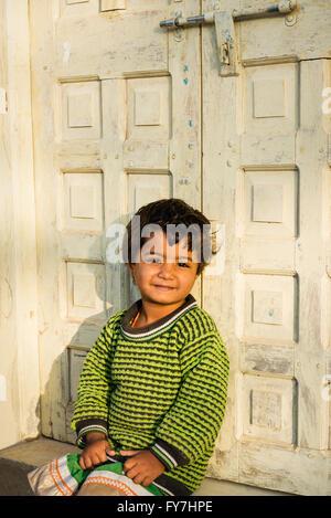 Garçon assis dans la porte de la Maison dans village de Chandelao Banque D'Images