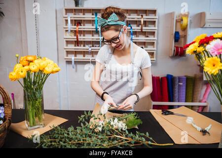 Smiling attractive young woman in glasses fleuriste bouquet et de rendre permanent in flower shop