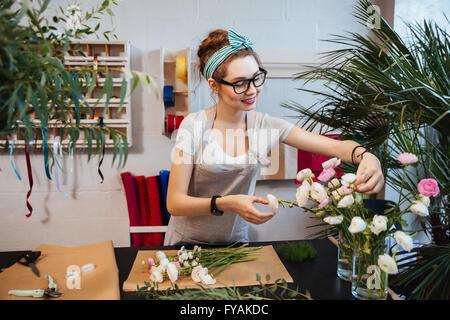 Smiling attractive young woman florist bouquet travailler et prendre dans le magasin de fleurs Banque D'Images