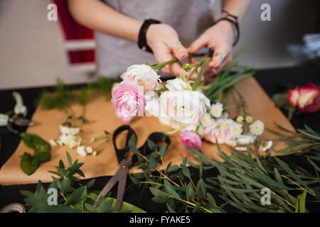 Libre de mains de jeune femme création fleuriste bouquet de roses sur la table Banque D'Images