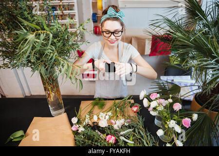 Belle jeune femme heureuse de prendre des photos de fleurs sur table dans la boutique Banque D'Images