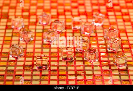Froid et humide des cubes de glace sur colorful glitter Banque D'Images
