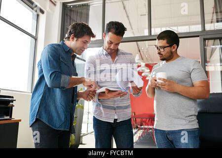 Les gens créatifs de discuter de projets dans une réunion au bureau permanent moderne. Concepteur de jeunes hommes Banque D'Images