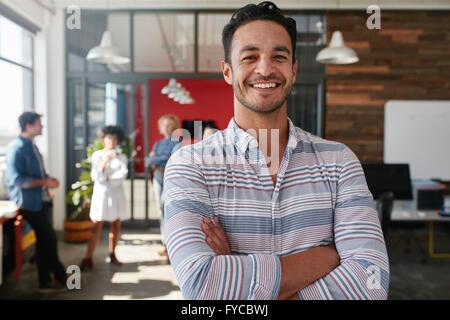 Portrait of a handsome man standing with arms crossed dans un bureau. Les jeunes hommes de race blanche intelligente Banque D'Images