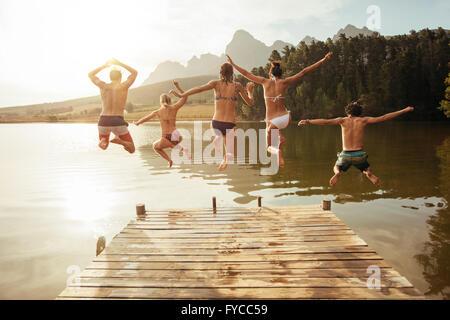 Portrait de jeunes amis sautant de la jetée dans le lac. Les amis au milieu de l'air sur une journée ensoleillée Banque D'Images