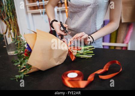 Libre de mains de jeune femme faire fleuriste arc avec ruban rouge bouquet de fleurs en boutique Banque D'Images