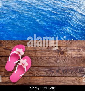Ordinateur tablette vide vide sur la plage. Accessoires d'été à la mode sur fond de bois extérieure. Les tongs sur Banque D'Images