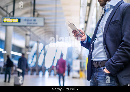 Close up of hipster businessman with smartphone, subway station Banque D'Images