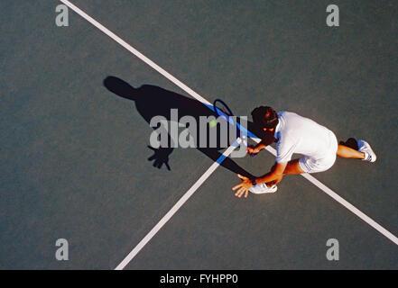 Vue supérieure de l'homme joueur de tennis frapper la balle avec une raquette Banque D'Images