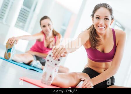 Souriante jeune femme à la salle de sport de faire un exercice d'étirement des jambes sur une natte, concept de Banque D'Images