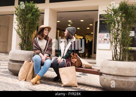 Amis de couple assis sur le banc de la ville Banque D'Images