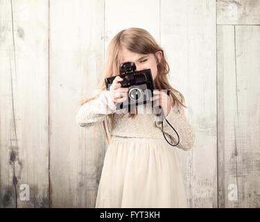 Un photographe de l'enfant est prise d'une photo avec un vieux film appareil contre un mur en bois blanc pour un Banque D'Images