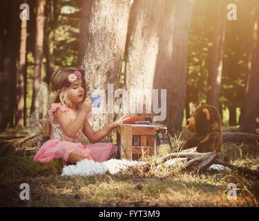 Une petite fée fille est assis dans les bois à jouer un jeu de cartes avec un ours en peluche pour une imagination Banque D'Images